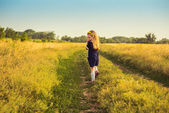The beautiful little girl in a blue dress laughs, holds hands at the person, looking back, goes to a field — Stock Photo