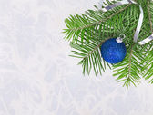 Christmas ball with fir-tree twigs on abstract background — Stock Photo