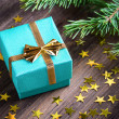 Christmas gift with stars and fir branch twig on wooden table — Stock Photo