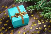 Regalo de navidad con estrellas y abeto rama rama en mesa de madera — Foto de Stock