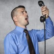 Angry businessman screaming during a telephone conversation — Stock Photo #49278319