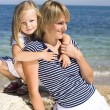 Young family having fun on beach, mother and daughter at sea — Stock Photo #37416379