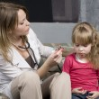 Stock Photo: Young doctor with little girl patient feeling bad medical inspection with stethoscope