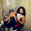 Stock Photo: Pretty young womin restroom with money, like prostitute