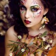 Stock Photo: Beauty womwith face art and jewelry from flowers orchids