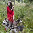 Woman in red dress with tree wolfs in forest — Stock Photo #37418259