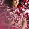 Stock Photo: Beautiful young womIn rose's petals