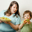 Fat woman holding salad and little cute boy with hamburger teasing — Stock Photo #37419073