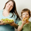 Fat woman holding salad and little cute boy with hamburger teasing — Stock Photo #37419081
