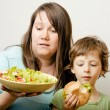 Fat woman holding salad and little cute boy with hamburger teasing — Stock Photo #37419107