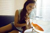 Linda mujer jugando con peces de colores en casa — Foto de Stock