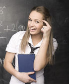 Portrait of pretty cute student with book near blackboard — Stock Photo