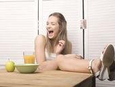 Portrait of funny teenage girl in white dress and sunglasses, having breakfast — Stockfoto