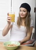 Portrait of funny teenage girl in white dress and sunglasses, having breakfast — Stock Photo