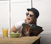 Portrait of funny teenage girl in white dress and sunglasses, having breakfast — Foto Stock
