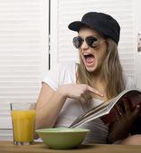 Portrait of funny teenage girl in white dress and sunglasses, having breakfast — Stock Photo
