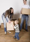 Stock-photo-smiling -family-in-new-hous e-playing-with-boxe s — Stock Photo