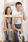 Portrait of happy family doing repair, standing near ladder — Stock Photo