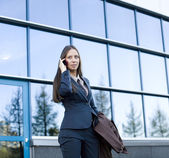 Portrait of pretty young business woman talking on phone — Stock Photo