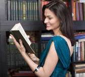 Stock photo portrait of beauty young woman reading book in library — Stok fotoğraf