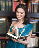 Stock photo portrait of beauty young woman reading book in library — Stockfoto