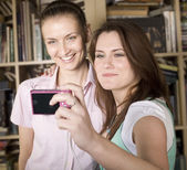 Stock-photo-happy-y oung-girls-making-f unny-face-while-tak ing-pictures-of-the mselves-through-cel lphone — Stock Photo