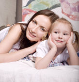 Happy family, mother and daughter in bed reading book and talking, laughing — Stock Photo