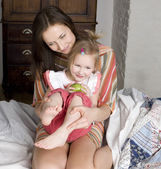 Portrait of happy mother and daughter in bed, smiling hugging, holding green apple — Stock Photo