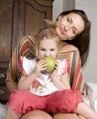 幸せで母と娘のベッド、笑みを浮かべて、ハグ青リンゴを保持の肖像画 — ストック写真
