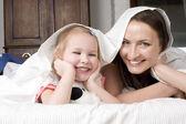 счастливая семья, мать и дочь в постели читать книгу и говорят, смеясь — Стоковое фото