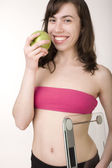 Girl wearing sports clothes holding scales and a measuring tape with green apple — Stock Photo