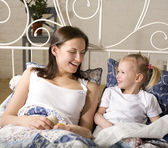 Portrait of happy family, mother and daughter in bed — Stock Photo