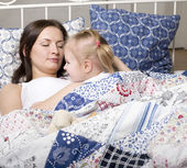 Portrait of happy family, mother and daughter in bed — Stockfoto