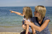 Young family having fun on the beach, mother and daughter at sea — Stock Photo
