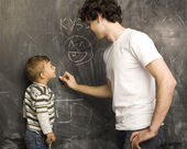 Portrait of teacher and little student, father and son near blackboard — Stock Photo