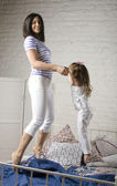 Portrait of happy mother and her daughter playing in bad — Stock Photo