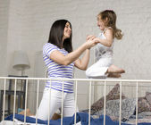 Retrato de mãe feliz e sua filha jogando em bad — Fotografia Stock