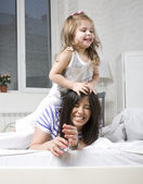 Portrait of happy mother and her daughter playing in bad — Stok fotoğraf