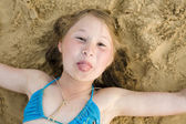 Portrait of little cute girl on sand having fun — Stock Photo