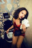 Pretty young woman in restroom with money, like prostitute — Zdjęcie stockowe