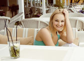 Portrait of pretty young girl in cafe drinking coctail and smiling — Stock Photo