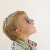 Little boy in sunglasses against white background — Stock Photo