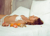Beauty woman in bed in white interior — Stock Photo