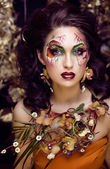 Beauty woman with face art and jewelry from flowers orchids — Stock Photo