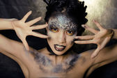 Fashion portrait of pretty young woman with creative make up like a snake — Stock Photo