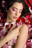 Beautiful young woman In rose's petals — Foto de Stock