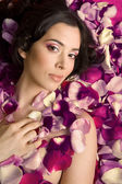 Beautiful young woman In rose's petals — Stockfoto
