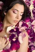 Beautiful young woman In rose's petals — Foto Stock
