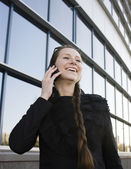 Portrait of pretty young business woman talking on phone near building — Stock Photo