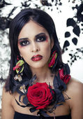 Pretty brunette woman with rose jewelry, black and red, bright make up kike a vampire — Stock Photo